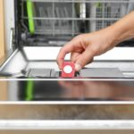 Image depicts woman putting detergent into her dishwasher.